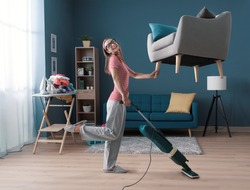 Efficient happy housewife cleaning up her apartment: she is lifting the armchair with one hand and vacuuming the floor, effortless easy housekeeping concept