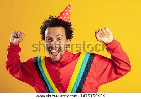 Efforts finally brought success. Overjoyed dark skinned woman celebrates party and clenches fists, shouts hooray, triumphs over win, cheers good results, isolated over purple studio background. #1475159636
