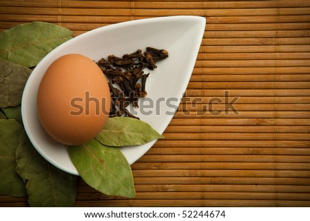 Egg and laurel leaves in a white container in the bamboo mat