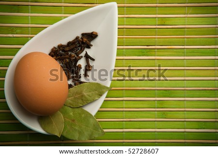 Egg and laurel leaves in a white container in the green bamboo mat