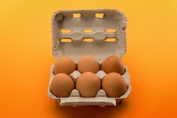 Egg box with eggs, six chicken eggs in cardboard egg tray made from recycled paper isolated on yellow orange background