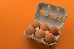 Egg box with eggs, six chicken eggs in cardboard egg tray made from recycled paper isolated on orange  background