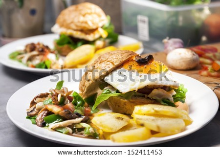 Egg burger , salad , boiled potatoes on kitchen background.