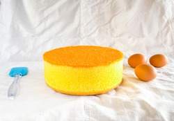Egg Cake 2 Lbs homemade round sponge cake or chiffon cake so soft and delicious with ingredients: eggs, flour, milk on wood table.