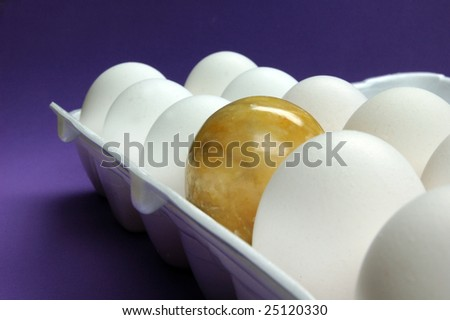 Egg carton filled with white eggs and golden marble egg