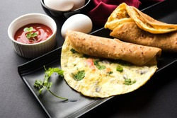 Egg Chapati - Omelette Roll or Franky. Indian Popular, quick and healthy recipe for kid's tiffin or lunch box. Served with tomato ketchup over moody background. Selective focus