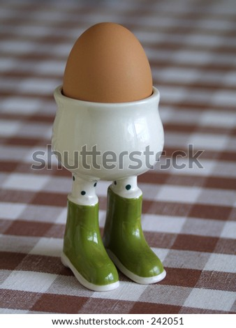 Egg in cup on check table cloth - stock photo