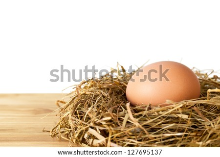 Egg in hay nest on wooden table against white background, isolated