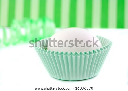 egg inside cupcake paper cup ready for baking with ribbon in the background