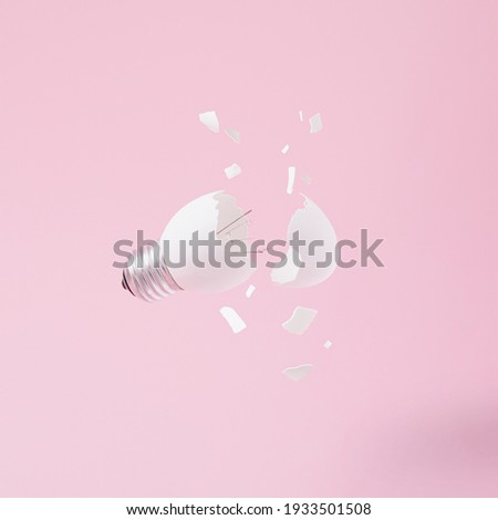 Egg lightbulb on pastel pink background with broken or shattered egg shell. Minimal concept. Easter inspiration. Flat lay. Foto stock ©