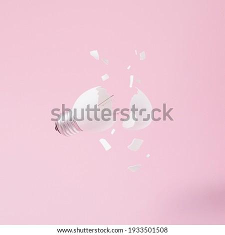Egg lightbulb on pastel pink background with broken or shattered egg shell. Minimal concept. Easter inspiration. Flat lay. Foto stock ©