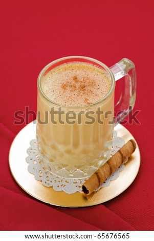 Egg nog in glass on gold coaster with cookie on red background.