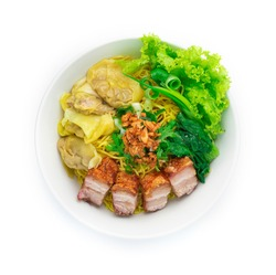 Egg Noodles with Crispy Roast Belly Pork and Wonton Dumplings ontop Crispy Garlic and Spring Onions in Bowl .Asian Food fusion style top view