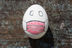 egg on wood with a red painted mask
