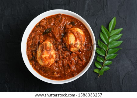 Egg roast curry or Mutta roast gravy dish popular spicy Kerala food on dark black background Tamil Nadu South India. Top view of Indian non veg side dish for rice, Appam, Chapati, Porotta, Parantha .
