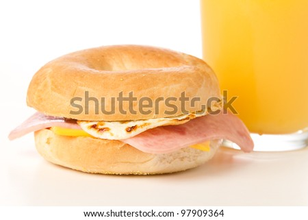 Egg Sandwich / This is a photo of a delicious egg, ham and cheese Sandwich on a toasted bagel with a glass of orange juice.