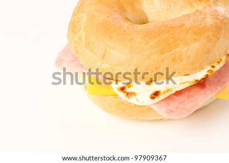Egg Sandwich / This is a photo of a egg ham and cheese sandwich on a toasted bagel. Shot on a white background.