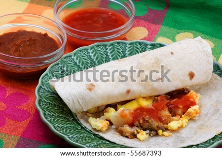 Egg, sausage and potato breakfast burritos on green plate setting on brightly colored place mat with individual servings of salsa and chili beans.