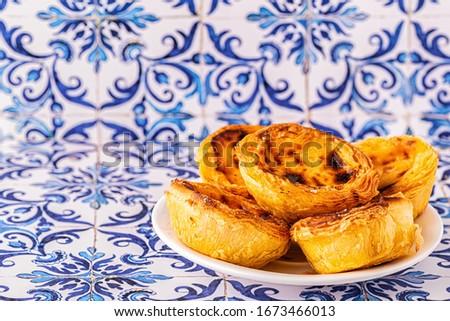 Egg tart, traditional Portuguese dessert, pastel de nata. Azulejo tile background. Foto stock ©
