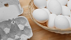 egg tray and wicker basket with plenty of white eggs on wooden table