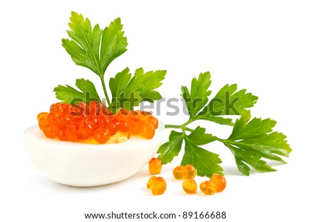 Egg with red caviar and parsley on a white background