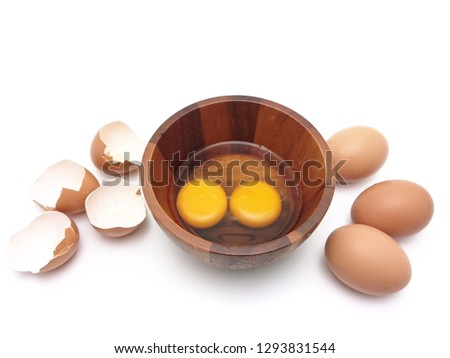 Egg yolk and Albumen in wooden bowl with eggs whole and eggshell isolated on white background