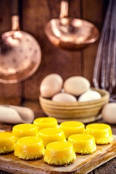 egg yolk candy, called Quindim in Brazil, and Portugal in brisa-do-Lis. Sweet dessert on rustic wooden background