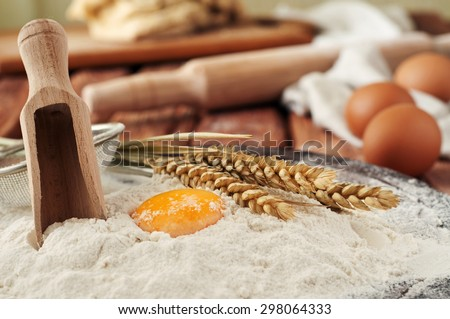 Egg yolk in flour close up on a wooden table in a bakery. Rural or rustic style. Copy space. Free space for text