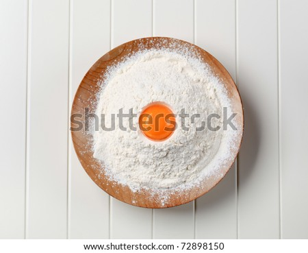 Egg yolk in the flour on the plate birds-view - stock photo