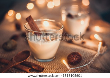 Eggnog in glasses with star anise and cinnamon on wooden table for Christmas and winter holidays. Copyspace included.