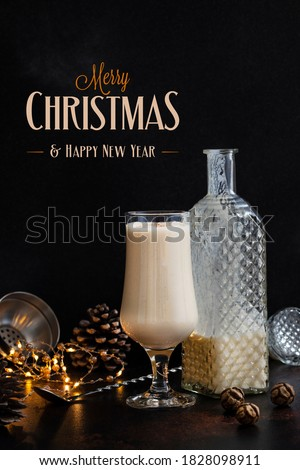 Eggnog traditional Christmas alcoholic drink with cinnamon and nutmeg. Eggnog in а glass and a bottle. Winter holidays mood. Christmas decorations and text - Merry Christmas and Happy New Year Сток-фото ©