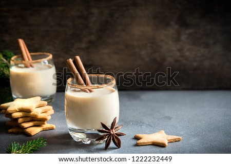 Eggnog with cinnamon and nutmeg for Christmas and winter holidays. Christmas Eggnog, gingerbread cookies isolated on stone background.