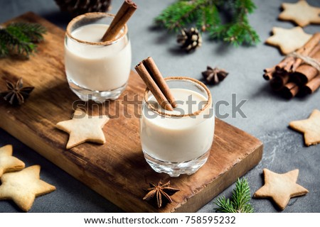 Eggnog with cinnamon and nutmeg for Christmas and winter holidays. Homemade eggnog in glasses with spicy rim.