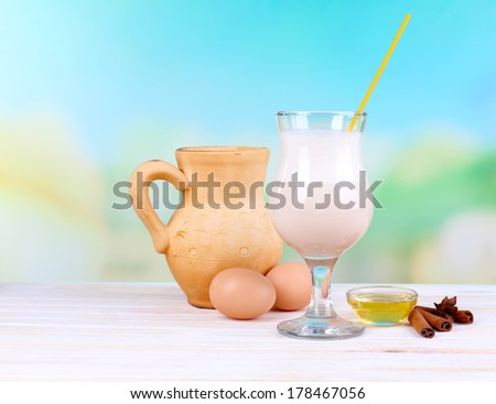 Eggnog with milk and eggs on wooden table and natural background