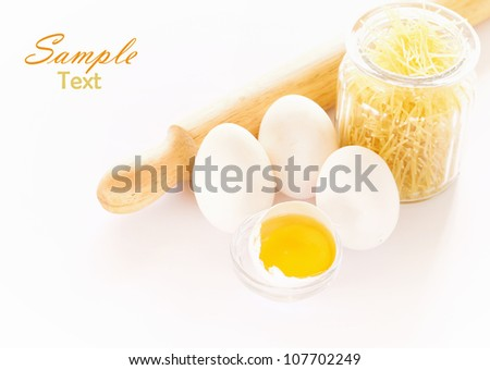 eggs and rolling pin over white background