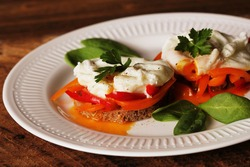 Eggs Benedict. Toasted muffins with paprika, spinach, poached eggs