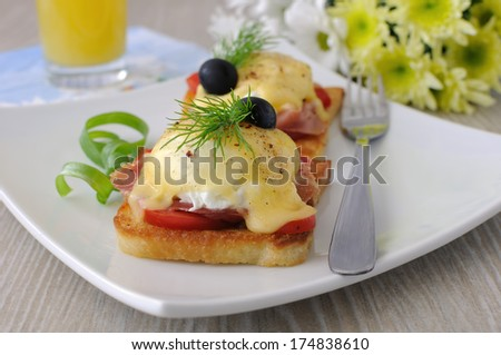 Eggs Benedict with ham and tomato on toast with cheese and orange juice - stock photo