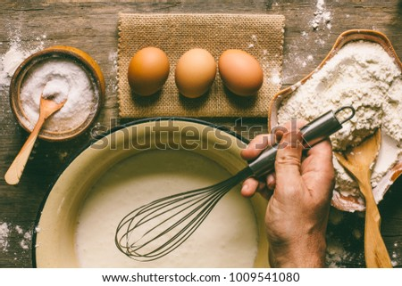 eggs, flour, and a male hand with a whisk dough top view. #1009541080