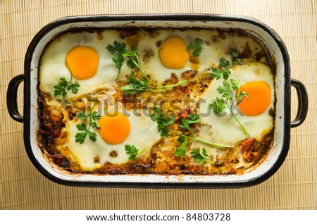 eggs fried with parsley on top of cooked rice meal
