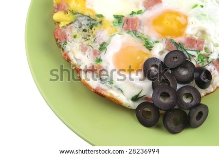 eggs fried with sausage and black olives on green dish