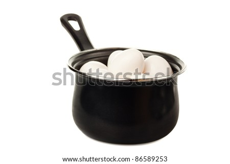 Eggs in a black cooking pot isolated on a white background - stock photo