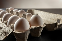 Eggs in a cardboard tray close-up with blurred depth of field and dimming on the sides