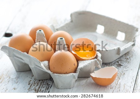 Eggs in a carton on a wooden background