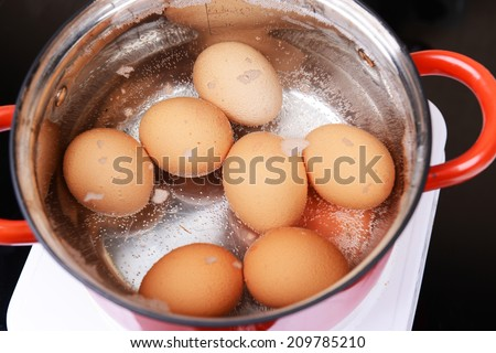 Eggs in boiling water in pan on electric hob