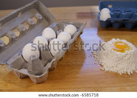 Eggs in carton with flour and egg for baking beside