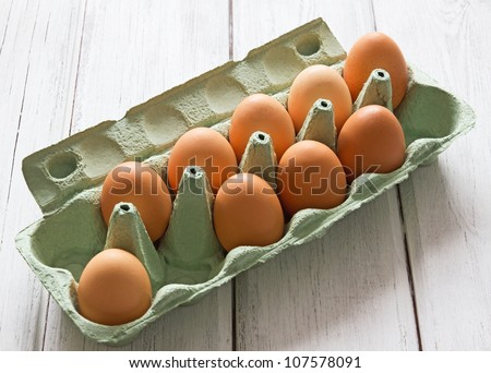 Eggs in egg-box on white wood background Nine fresh chicken eggs in green egg-box on white painted wooden background.