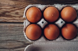 eggs in paper on wooden background