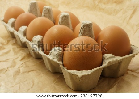 Eggs in the package on a brown paper.  Selective focus
