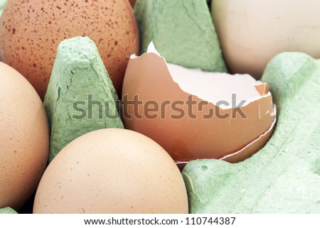 Eggs still in carton, one has been opened.
