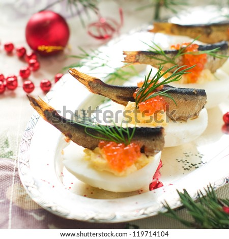 Eggs stuffed with yolk, caviar and fish, selective focus